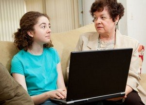 mother and teen daughter discussing computer use